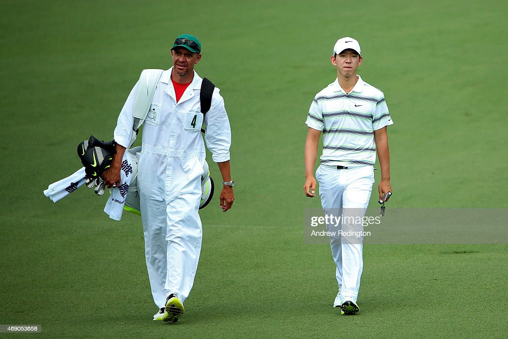 SeungYul Noh of Korea and caddie David Brooker walk up the second hole during the first round of the 2015 Masters Tournament at Augusta National Golf...