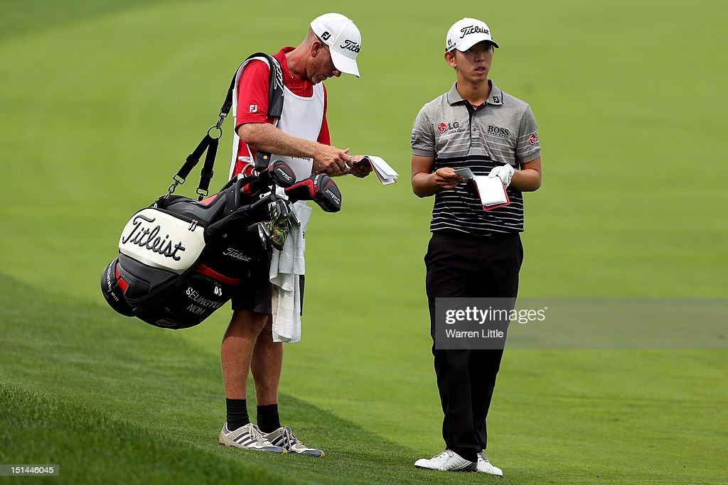 Seung-Yul Noh of Korea talks with his caddie on the fairway prior to attempting his second shot on the fifth hole during the second round of the BMW Championship at Crooked Stick Golf Club on September 7, 2012 in Carmel, Indiana.