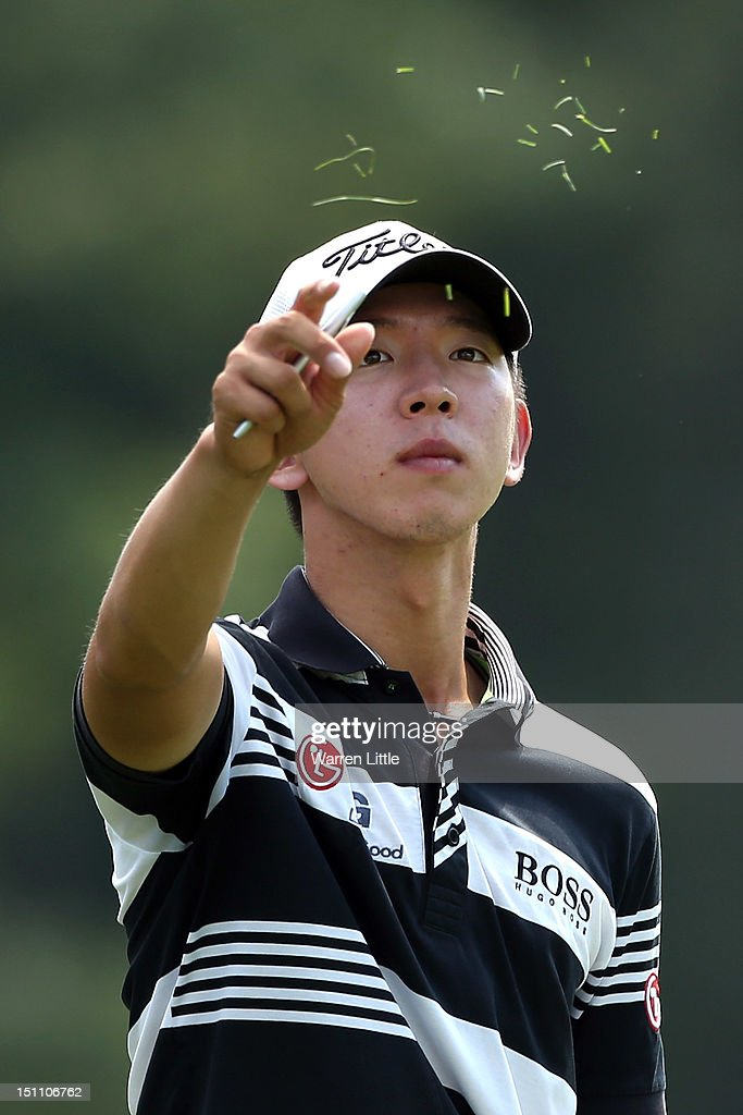 Seung-Yul Noh of South Korea throws blades of grass into the air to check the wind while on the ninth hole during the second round of the Deutsche Bank Championship at TPC Boston on September 1, 2012 in Norton, Massachusetts.