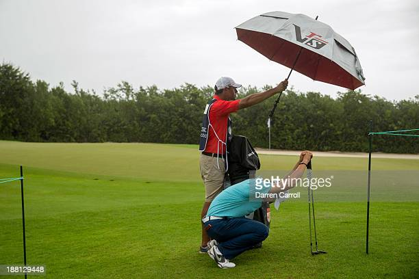 SeungYul Noh of South Korea waits at the 16th hole during weather delay in the second round of the 2013 OHL Classic at Mayakoba played at El Camaleon...