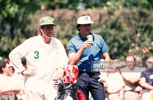 Seve Ballesteros watches out over the field along side his caddie in front of a small gallery during the 1986 Masters Tournament at Augusta National...