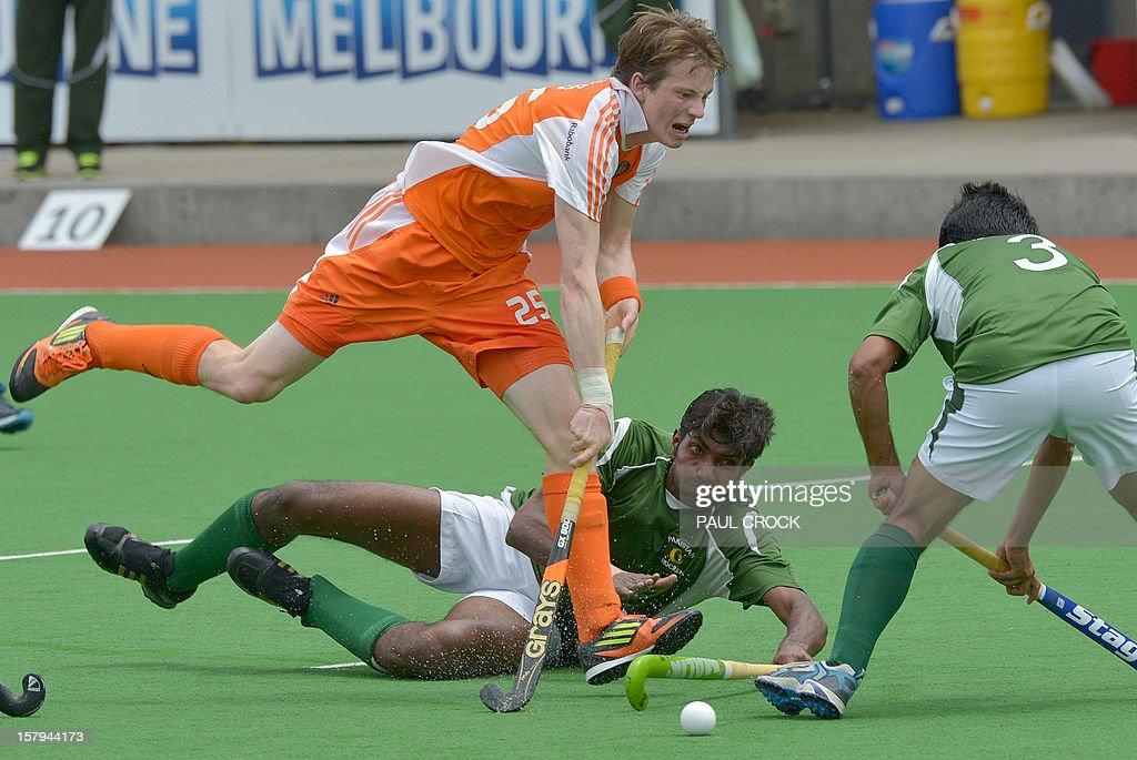 Seve van Ass of The Netherlands (L) leaps through defenders Ahmed Waseem (R) and Muhammad Ateeq of Pakistan (C) during their semi final match at the Men's Hockey Champions Trophy in Melbourne on December 8, 2012. IMAGE STRICTLY RESTRICTED TO EDITORIAL USE - STRICTLY NO COMMERCIAL USE AFP PHOTO/Paul CROCK