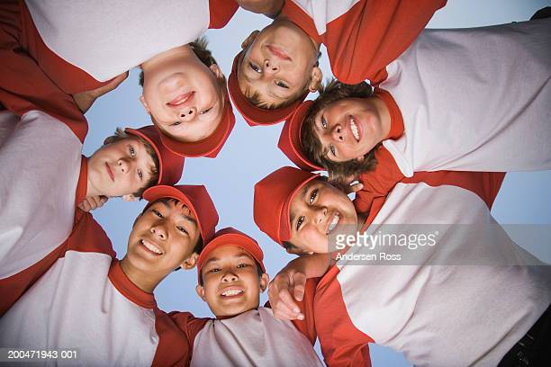 Seven baseball players (9-14) standing in huddle, view from below