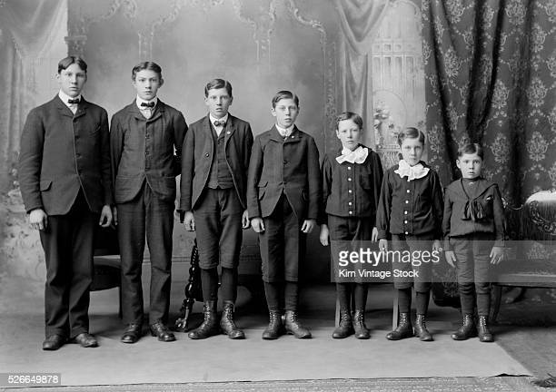 Seven brothers stand in descending order of age and height for a formal family portrait at the turn of the 20th century