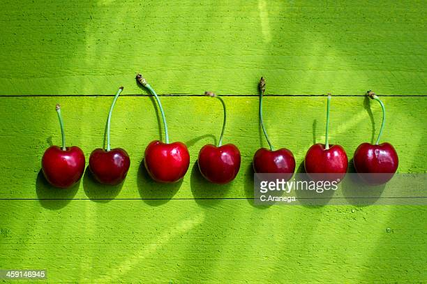 Seven cherries on a green background