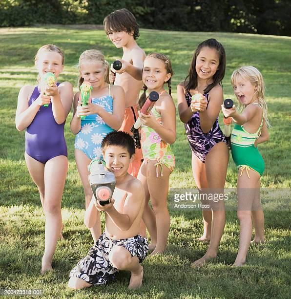 Seven children (7-12) holding squirt guns outdoors, portrait