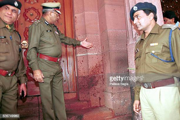 Seven civilians and five terrorists were killed in a suicide attack on the Indian Parliament Senior police officers examine the blood that was...