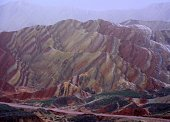 Colourful rocks at the fourth viewing platform looking Qicai Shan (seven colour Mountain). Danxia landform geological park, near the town of Zhangye. Known for its colorful rock formations, has unusua