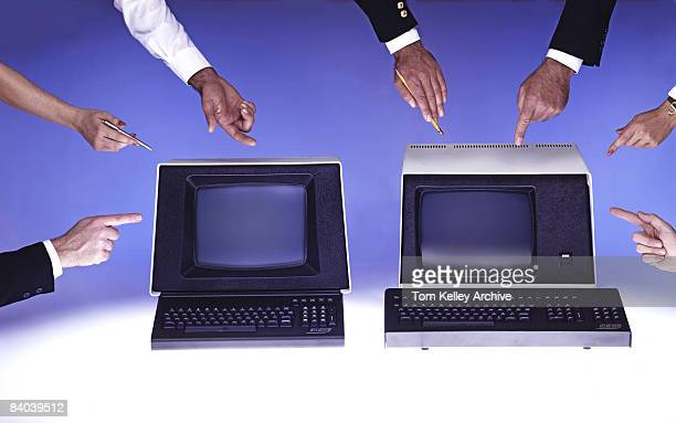 Seven different hands point at two older computer terminals ca1980s United States
