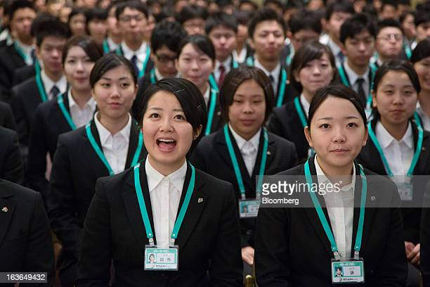 A Seven I Holdings Co new employee front left responds to a greeting practice prior to an initiation ceremony in Tokyo Japan on Thursday March 14...