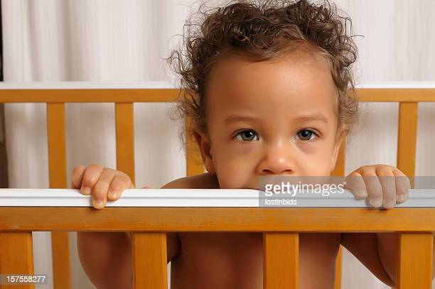 Seven month old baby standing in his cot