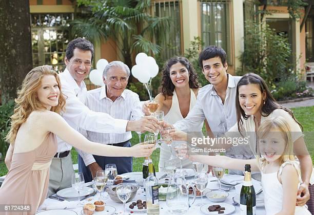 Sete pessoas ao ar livre em uma festa de tostar bebidas e sorrir