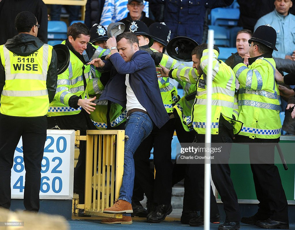 Seven police officers remove a Millwall fan from the stand during the npower Championship match between Millwall and Leeds United at The New Den on November 18, 2012 in London, England.