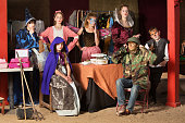 Seven young theater students prepare in the dressing room wearing their costumes