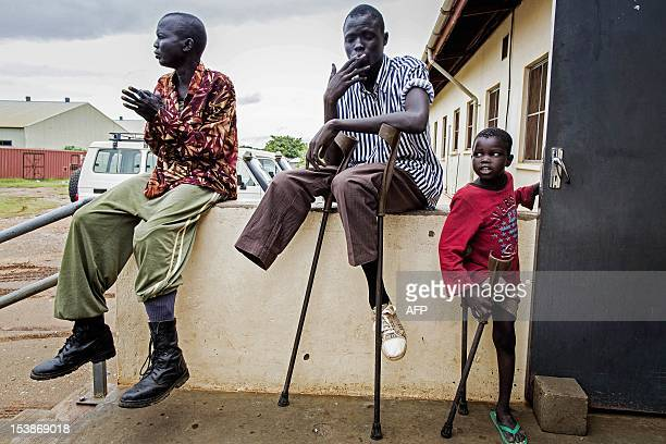 Seven year old amputee Deng SPLA soldier Kong and Mabior are pictured at the Rehabilitation Centre of Juba South Sudan on October 10 2012 Deng was...