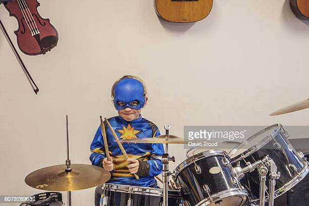 Seven year old boy in costume playing drums