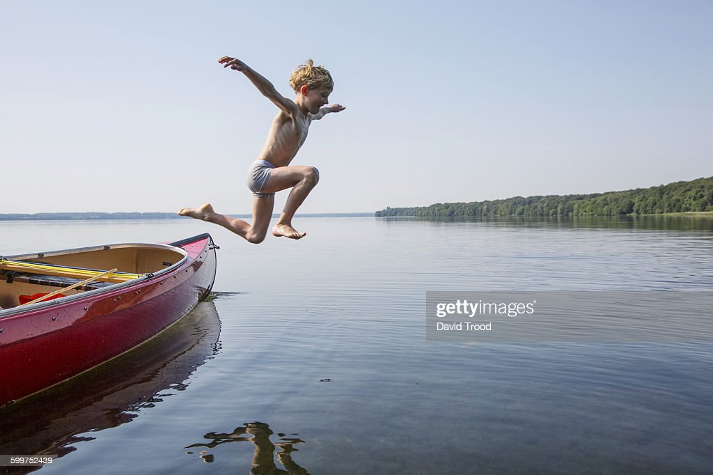 Seven year old boy jumping from a canoe. : Stock Photo
