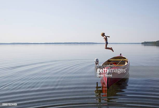 Seven year old boy jumps into a lake from a canoe.