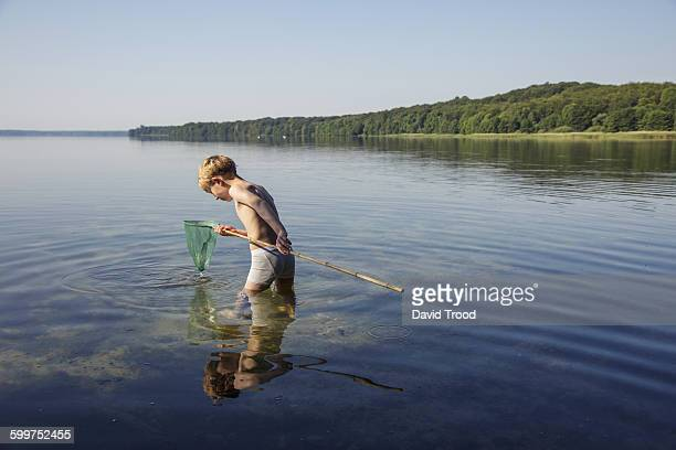 Seven year old boy playing with fish net.