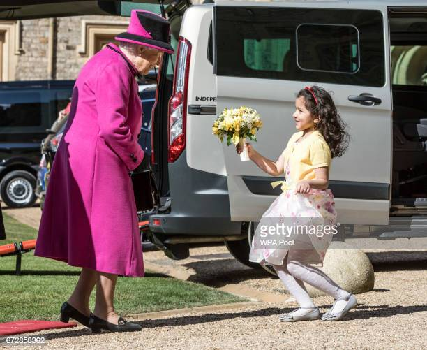 Seven year old Dina Rayburn presents Queen Elizabeth II with flowers during a ceremony during a ceremony on April 25 2017 in Windsor United Kingdom...