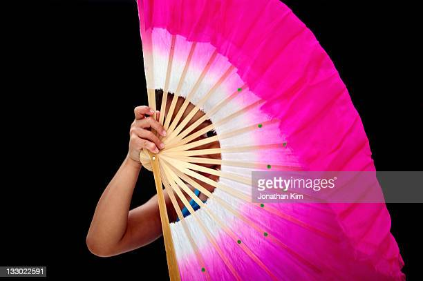 Seven year old girl hides behind a fan.