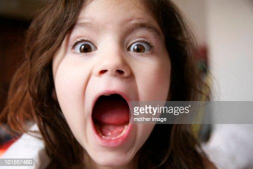 Seven year old girl yelling at camera : Stock Photo