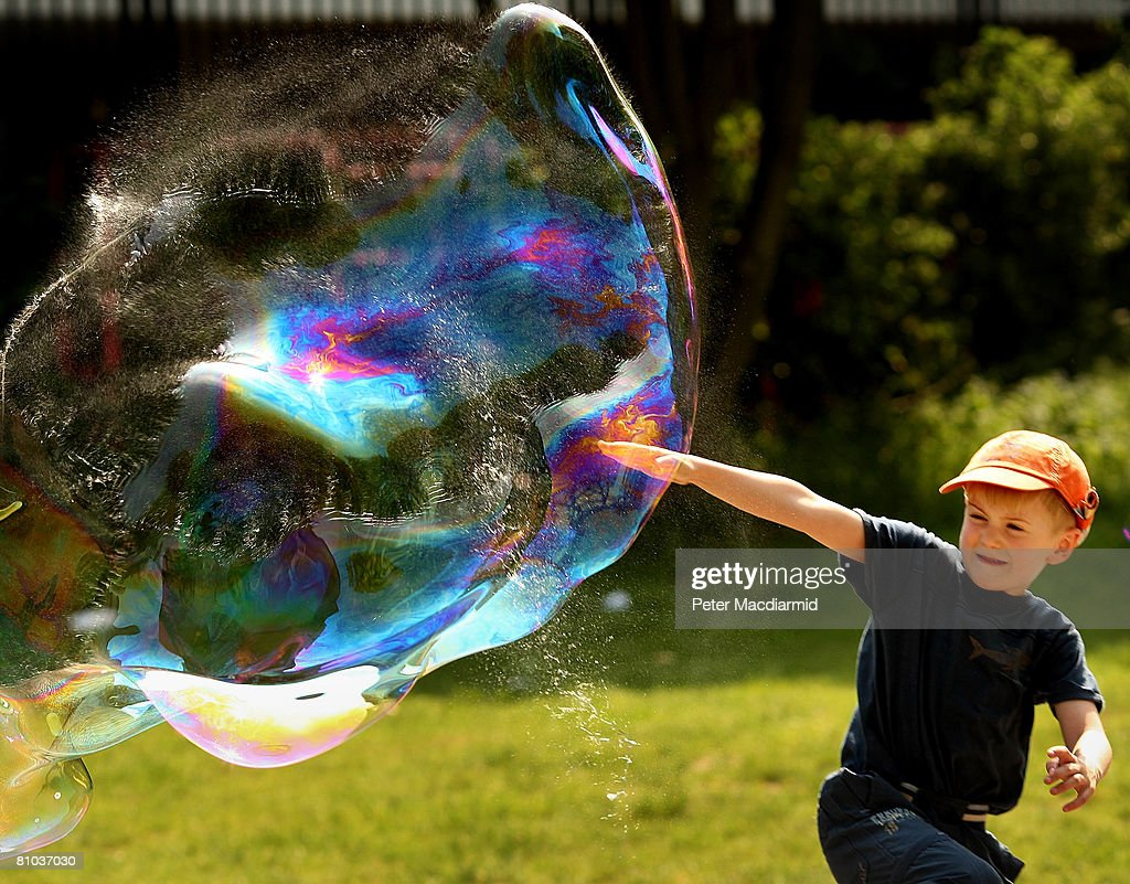 Seven year old Jacob Stanley, from Dublin, reaches up to puncture a giant bubble on London's South Bank on May 9, 2008 in England. The south east of England has enjoyed higher than normal temperatures.
