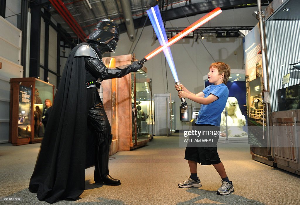 Seven yearold Jet Wigley takes on Darth Vader with a 'lightsaber' at the launch of 'Star Wars Where Science Meets Imagination' exhibition developed...