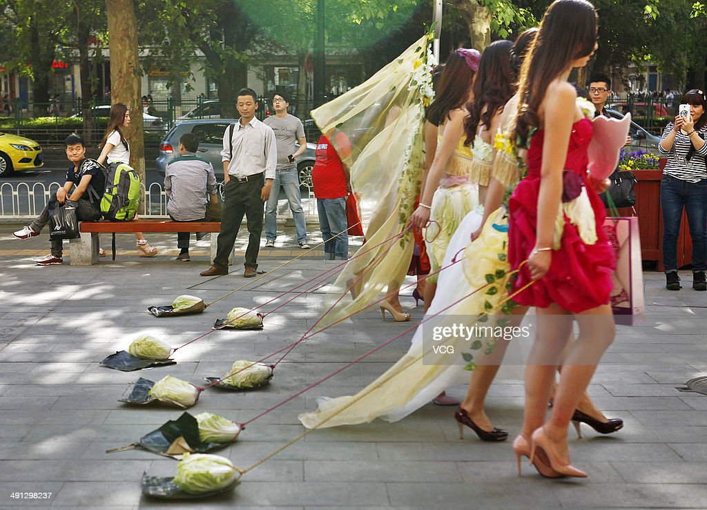 Seven young women walk with cabbages on leashes at the street of Xiaozhai on May 15, 2014 in Xi'an, Shannxi Province of China. 'Walking' cabbages on leashes were allegedly doing so as a means to deal with loneliness and depression. The performance was based on the work of Chinese artist Han Bing's photo series 'Walking the Cabbage'.