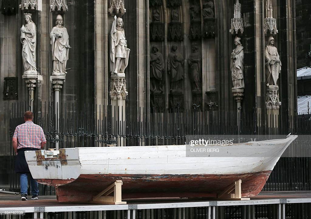 A seven-meter-long refugee boat is pictured on May 25, 2016 in front of the cathedral in Cologne. Archbishop of Cologne, Cardinal Woelki wants to celebrate the Corpus Christi Mass at the boat in memory of thousands of migrants who lost their lives in the Mediterranean sea. / AFP / dpa / Oliver Berg / Germany OUT