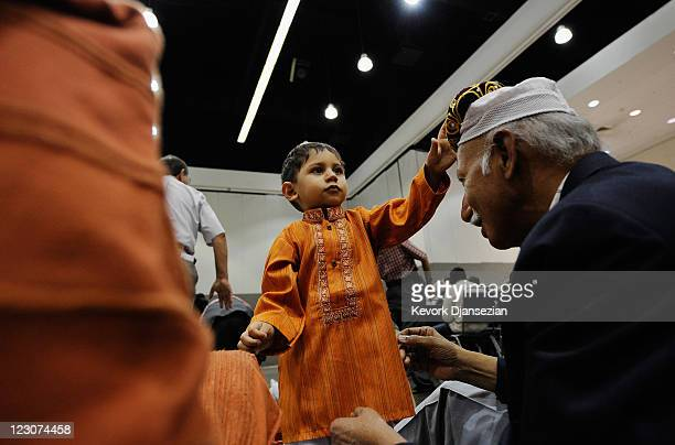 Seventeen months old Pakistani Muslim Ali Khaja gives his hat to his grandfather Ahsan Khaja before for the special Eid ulFitr morning prayer at the...