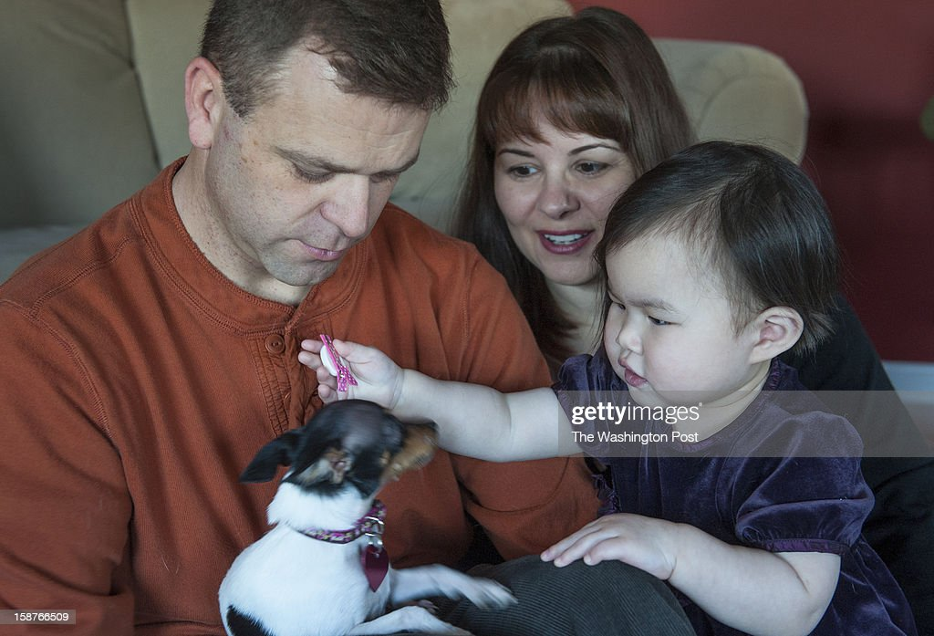 Seventeen-month-old Hannah tries to put her barrett onto Penny, the dog, as Adam and Carol Raines watch Sunday, December 23, 2012 in Westminster, MD. The couple, who have been together 16 years, adopted Hannah from Korea and just brought her home two weeks ago.