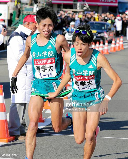Seventh runner Kazuki Tamura of Aoyama Gakuin University passes the sash to eighth runner Yuta Shimoda during day two of the 93rd Hakone Ekiden on...