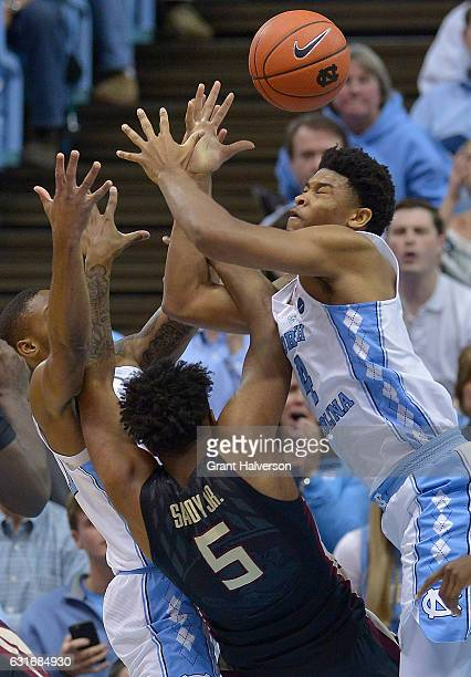 Seventh Woods and Isaiah Hicks of the North Carolina Tar Heels battle PJ Savoy of the Florida State Seminoles for a rebound during the game at the...
