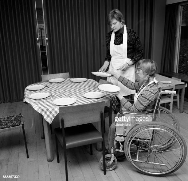 Seventies black and white photo people physical handicap school school lessons cooking instruction two schoolgirls 13 to 16 years laying the table...