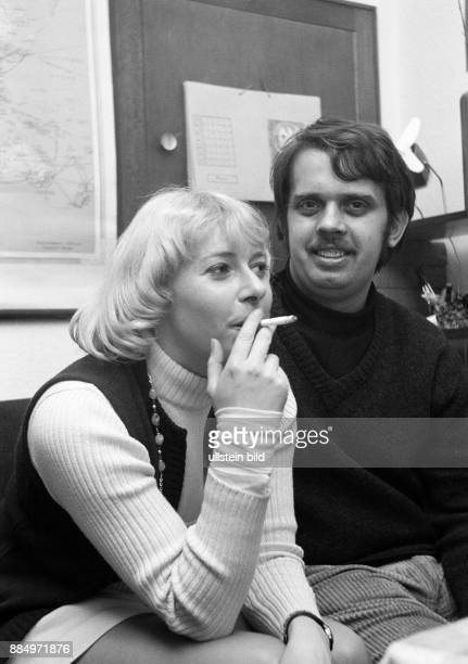 Seventies black and white photo people young couple sitting in the living room woman 20 to 25 years smoking a cigarette man 25 to 30 year sitting...