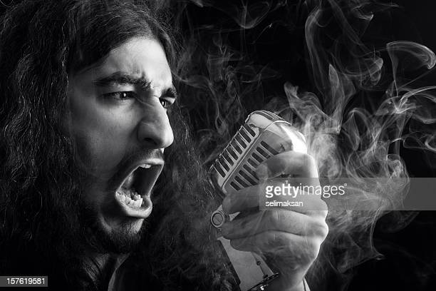 Seventies rock star singing on old fashioned microphone in smoke