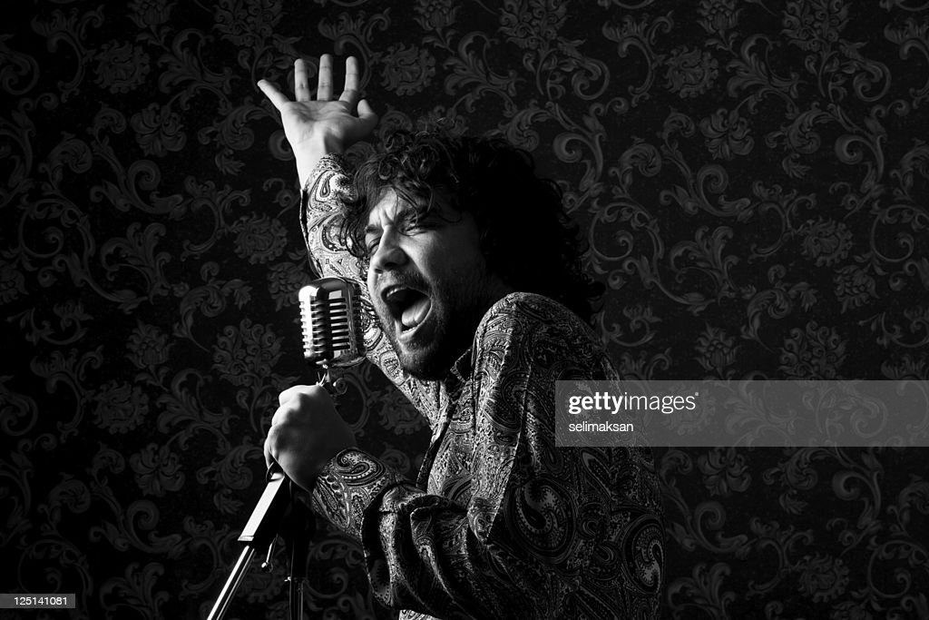 Seventies rock star singing on old fashioned microphone : Stock Photo