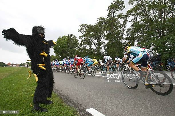 Seventime Tour de France winner and Kazakh cycling team Astana 's Lance Armstrong of the United States rides past a fan dressed up as a monkey on...