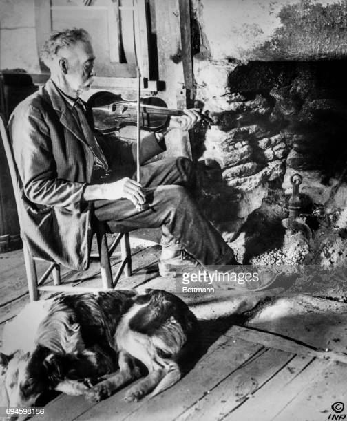 Seventy seven year old man fiddles by the fire with his dog nearby The fire in his home in North Carolina has burned for 147 years