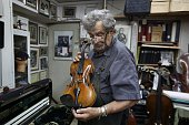Seventysixyearold Israeli violin maker Amnon Weinstein holds a violin which he named the 'Auschwitz Violin' since it belonged to a Jewish man...