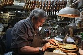 Seventysixyearold Israeli violin maker Amnon Weinstein restores an old violin at his workshop in Tel Aviv on July 15 2016 Weinstein a relative of...