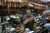 Seventysixyearold Israeli violin maker Amnon Weinstein shows a violin from his collection of restored violins that were formerly owned by European...