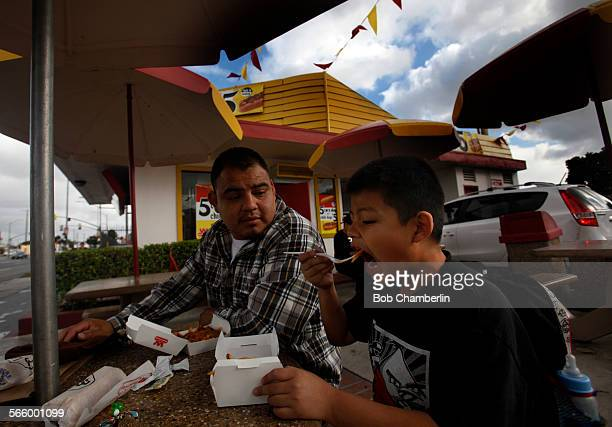 Sevenyearold Joseph Cruz right digs into his chili cheese fries as he has lunch with his father Jose Cruz center at the first roadside stand opened...