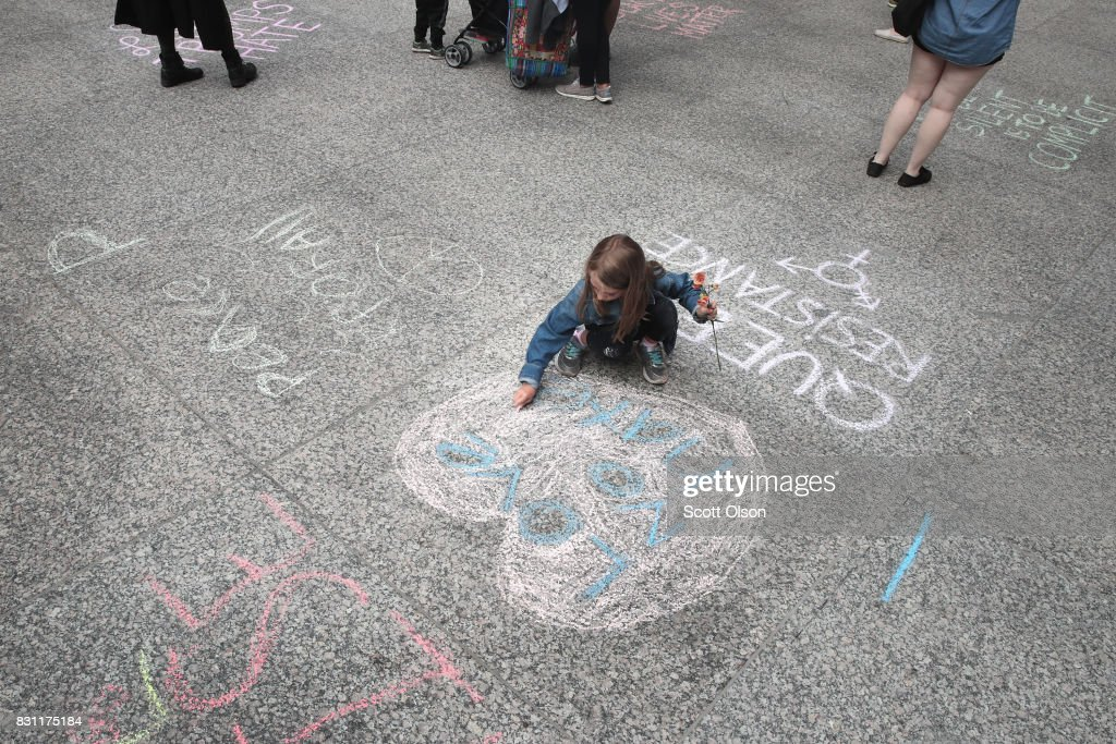 Seven-year-old Julia Manthei chalks 'Love Not Hate' onto the plaza before the start of an event to protest against the alt-right movement and to mourn the victims of yesterdays rally in Charlottesville, Virginia on August 13, 2017 in Chicago, Illinois. One person was killed and 19 others were injured in Charlottesville when a car plowed into a group of activists who were preparing to march in opposition to a nearby white nationalists rally. Two police officers were also killed when a helicopter they were using to monitor the rally crashed.