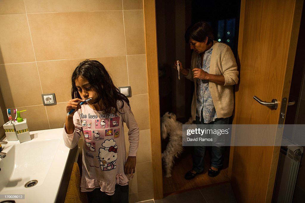 Seven-year-old Katalina brushes her teeth as her fifty-year old grandmother Doris Perez plays with their pet dog at the apartment of an occupied newly constructed building where Doris Perez moved last March with her three grandchildren after they were evicted a year ago after being unable to afford their rent on June 4, 2013 in Salt, Spain. In 2010 Spanish banks foreclosed on more than 100,000 households contributing to the already large number of empty houses in Spain. With as many as one million properties unsold victims of Spain's financial crisis have turned to squatting in the empty buildings. This building has stood empty for two years before the anti-eviction platform of Girona and several homeless families moved in three months ago. The community houses a total of 8 families who have to suffer water and electricity cuts and live with the fear of eviction.