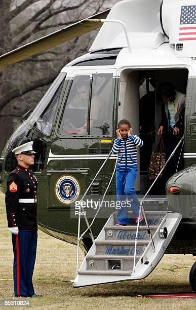 Sevenyearold Sasha Obama puts her hands over her ears as she US President Barack Obama first lady Michelle Obama and tenyearold Malia Obama return...