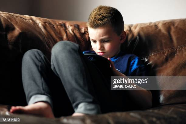 Sevenyearold transgender boy Jacob Lemay plays with an iPad in his home in Melrose Massachusetts on May 9 2017 For months in the Lemay home the same...