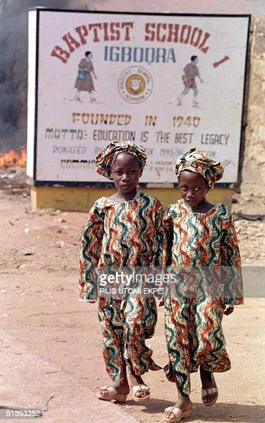 Sevenyearold twin sisters Seye and Sayo step out 31 March 2001 to attend a party in the southwestern Nigerian town of IgboOra Population experts...