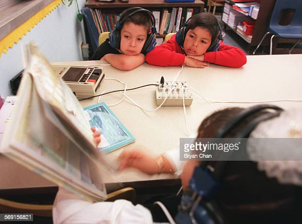 Seven–year–olds Juan Navarro left and Jose Ortega listen to an audio version of a children's book as they read along in Ana Hunt's second grade class...